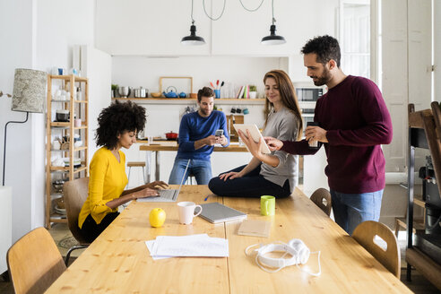 Four friends in dining room at home with portable devices - GIOF06445