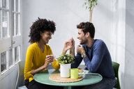 Happy affectionate couple sitting at table at home - GIOF06448