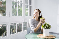 Young woman stting at the window at home with coffee cup and headphones - GIOF06451