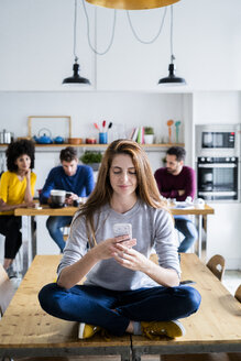 Woman with cell phone sitting on dining table at home with friends in background - GIOF06463
