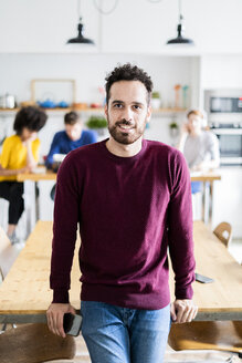Portrait of smiling man at dining table at home with friends in background - GIOF06466
