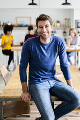 Portrait of smiling man at dining table at home with friends in background - GIOF06469