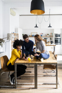 Three friends sharing cell phone on dining table at home - GIOF06472