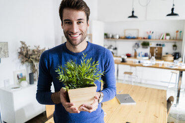 Portrait of smiling young man holding plant at home - GIOF06478