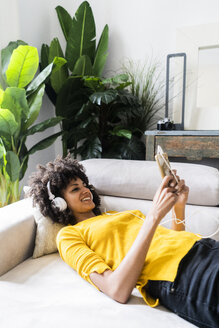 Smiling woman lying on couch with cell phone and headphones - GIOF06487