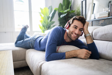 Relaxed man lying on couch listening to music - GIOF06490