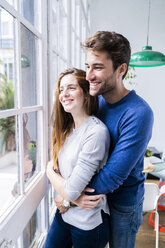 Happy affectionate couple hugging at the window at home - GIOF06496