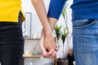 Close-up of couple holding hands at home - GIOF06499