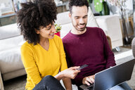 Happy couple at home shopping online with laptop and credit card - GIOF06502