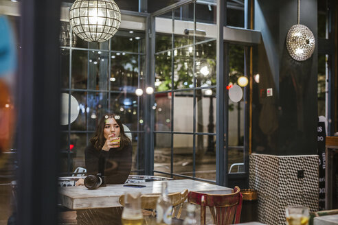 Young woman with camera in a bar at night - LJF00103