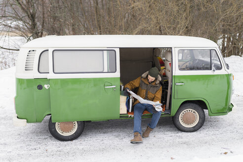 Man with electric van in winter landscape studying road map, Kuopio, Finland - PSIF00282
