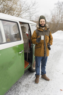Portrait of smiling man with electric van in winter landscape, Kuopio, Finland - PSIF00285
