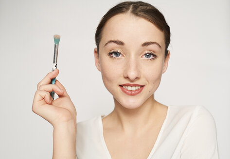 Portrait of smiling young woman with beauty brush - PNEF01536