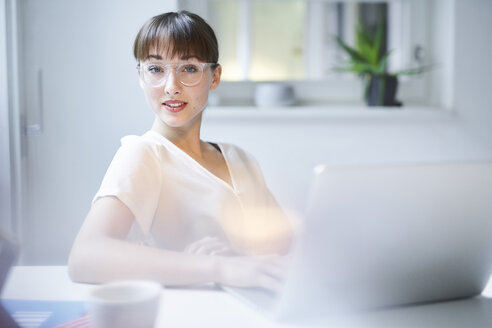 Portrait of young businesswoman with laptop sitting at desk in an office - PNEF01548