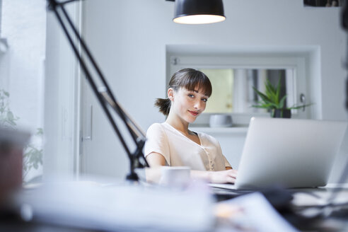 Portrait of smiling young businesswoman working on laptop in an office - PNEF01551