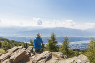 Hiker resting at Almbrunn hiking trail, Lammersdorf Mountain, Nock Mountains, Carinthia, Austria - GWF06085