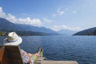 Man resting at lakeshore, Seeboden, Millstatt Lake, Carinthia, Austria - GWF06100