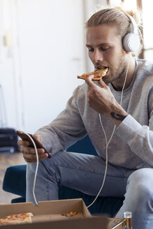 Young man on couch with cell phone and headphones eating pizza - JSRF00182