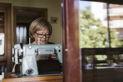 Senior woman using an sewing old machine at home - LJF00113