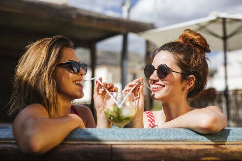 Two women having a drink in a jacuzzi - LJF00134