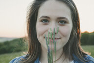 Portrait of smiling teenage girl with grasses at sunset - ANHF00107