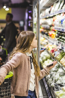 Side view of girl looking at vegetables on shelves in store - MASF12434