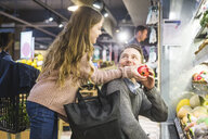 Side view of smiling daughter giving pomegranate to father while shopping in store - MASF12437