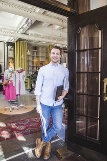Full length portrait of confident smiling owner standing in clothing store - MASF12440