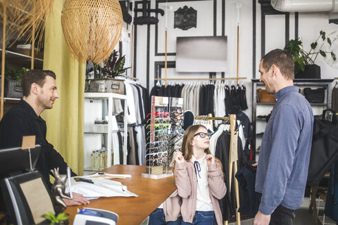 Cute daughter trying eyeglasses while looking at father by checkout counter in boutique - MASF12455