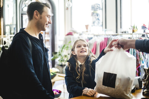 Cute daughter receiving shopping bag from cashier by father at checkout counter - MASF12458
