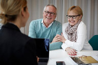 Happy senior couple talking to real estate agent in office - MASF12479