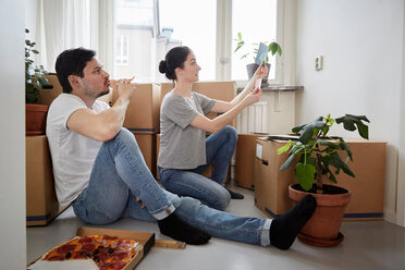 Man eating pizza while looking at woman choosing color swatches in new house - MASF12503
