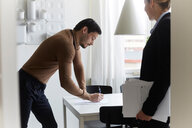 Mid adult man signing document while standing by real estate agent at new home - MASF12536