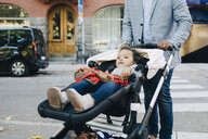 Father pushing daughter in carriage on street at city - MASF12548