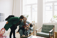Couple kissing while daughter drinking milk in living room at home - MASF12566