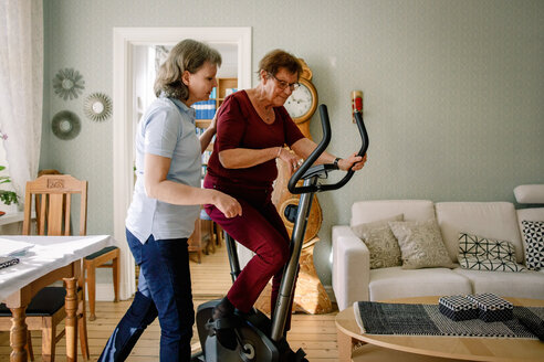 Mature female physical therapist assisting elderly woman on exercise bike at nursing home - MASF12575