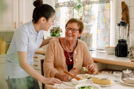Cheerful senior woman talking with female caregiver in kitchen at nursing home - MASF12590