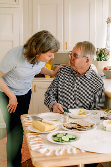 Mature female caregiver talking with retired senior man sitting at table for breakfast in nursing home - MASF12593