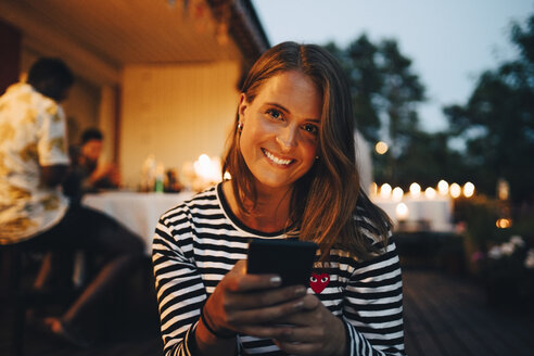 Portrait of smiling woman holding smart phone while friends in background during dinner party - MASF12608