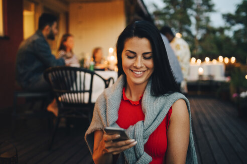 Smiling mid adult woman using mobile phone while friends in background during dinner party - MASF12620