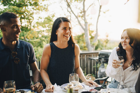 Smiling male and female friends enjoying food at dining table in dinner party - MASF12659