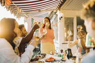 Multi-ethnic friends raising toast while enjoying in dinner party at yard - MASF12665