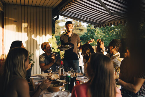 Friends at dining table clapping for man serving food in dinner party - MASF12671