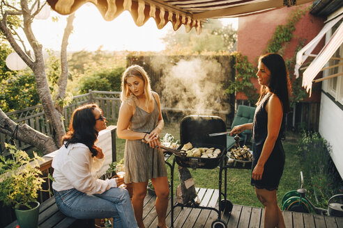 Friends talking while grilling food on barbecue for dinner party in yard - MASF12677