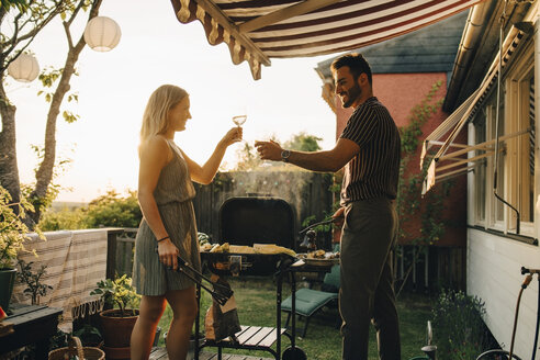 Happy friends raising toast while preparing food on barbecue grill in dinner party - MASF12680