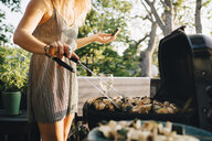 Midsection of woman grilling vegetables on barbecue while eating watermelon - MASF12683