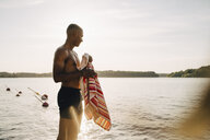 Smiling shirtless wet man with towel looking at lake in summer - MASF12704