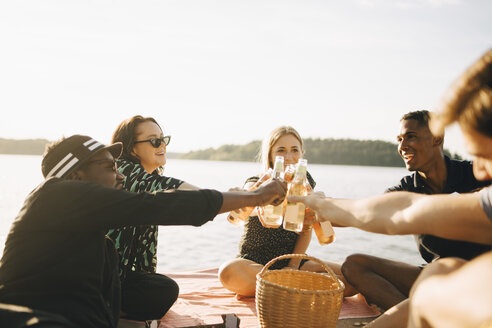 Friends toasting bottles while sitting on jetty against sky in summer - MASF12713