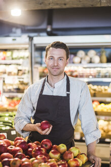 Portrait of confident smiling entrepreneur holding apple while standing in supermarket - MASF12755