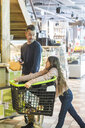 Father talking to cute daughter leaning on shopping cart at supermarket - MASF12767